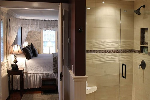 Lady Mariah guest room showing view from bathroom to bedroom with double shower and view of king canopy bed