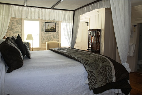 Lady Mariah guest room showing king bed with white bedding and gathered canopy draping and wingback reading chairs in background