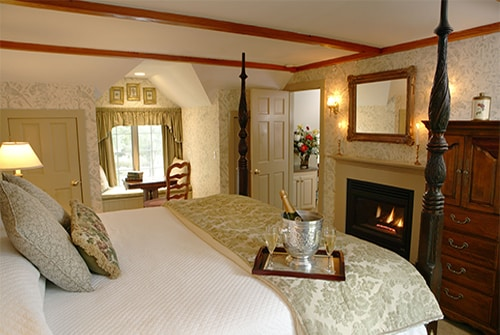 Lydia Harding Suite bedroom showing king bed with sage and beige bedding and champagne and gas fireplace