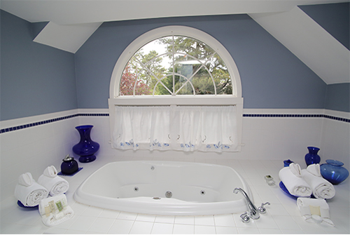 Beautiful pale blue and white bathroom with soaking tub, white tile and towels, blue vases and arched window