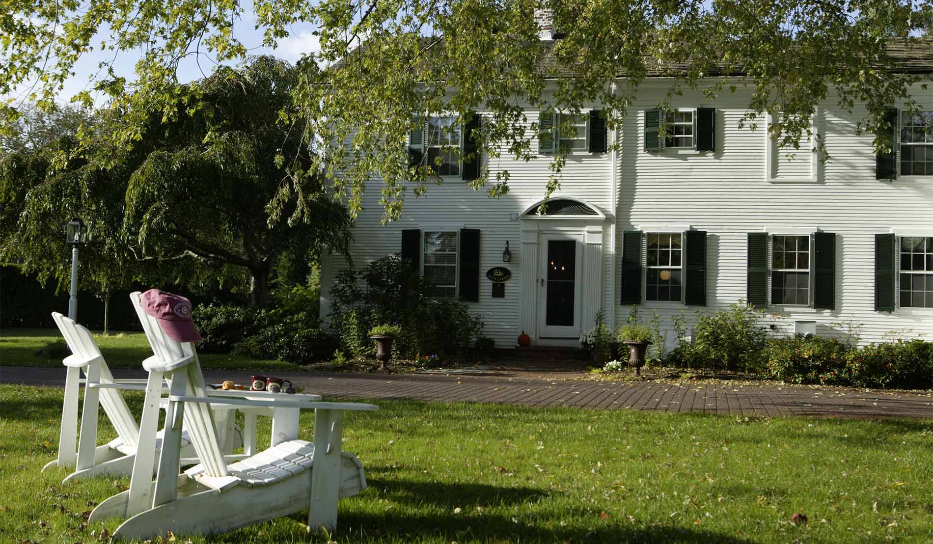 Exterior of Main House with lush, green trees and white Adirondack chairs