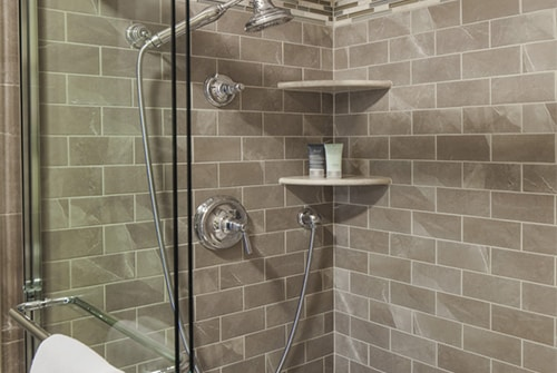 Northern Light double shower with grey and brown tiles and multiple shower heads