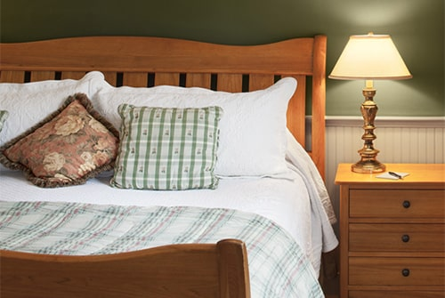Northern Light guest room showing cherry king sleigh bed and matching night side table