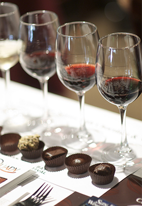 Row of wine glasses with red wine and pieces of chocolate