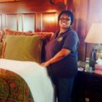 Woman standing next to a nicely made guest room bed