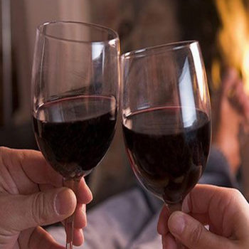 Two people holding wine glasses filled with red wine