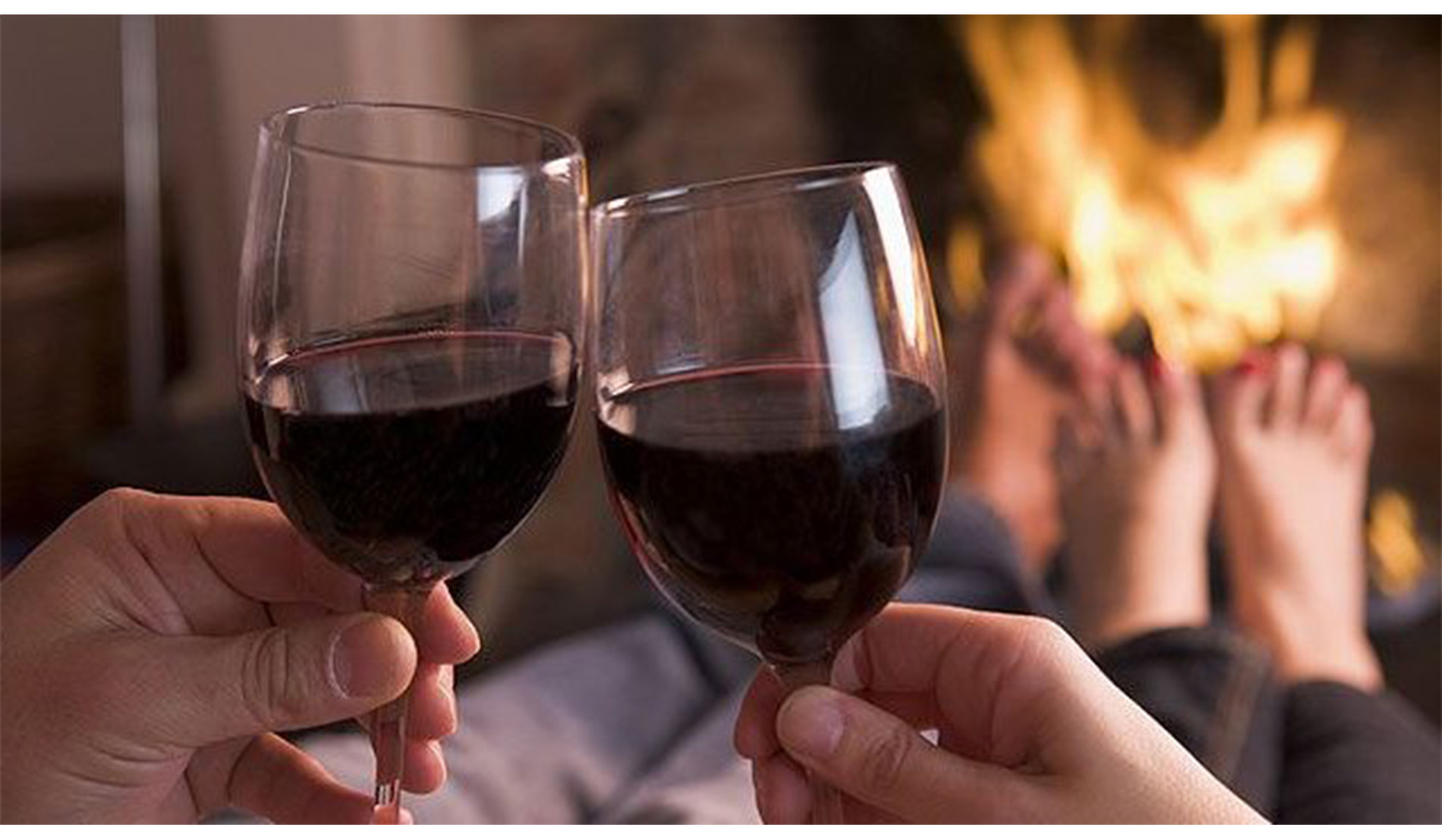 Couple in front of fireplace toasting with red wine in glasses