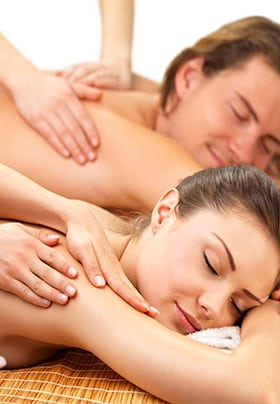 Man and woman smiling face down with their eyes closed receiving a couple's massage