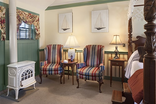 Tradewinds guest room showing striped wingback reading chairs and white enamal potbelly stove gas fireplace.