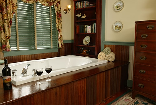 Tradewinds double soaking tub with wood deck surround and red wine