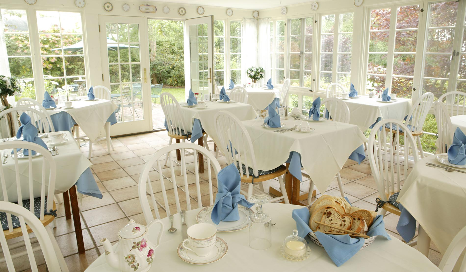 Dining room showing windows on three sides with tables with white table linens and blue napkins