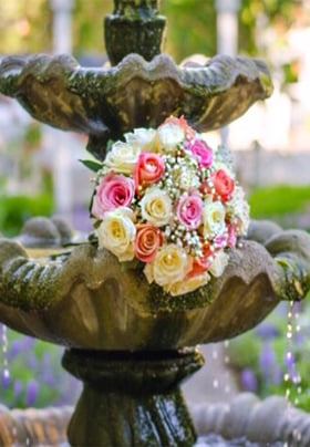 Beautiful pastel bouquet of roses on a tiered water fountain