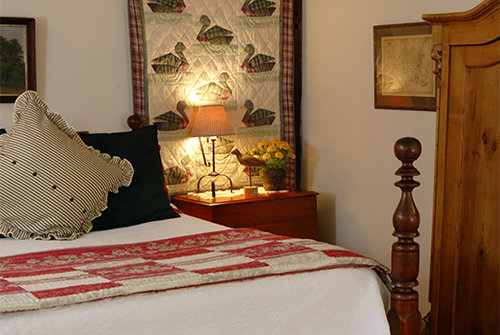 Whirlwind guest room showing queen bed with red quilted bedding, quilted wall hanging, and night side table with reading light