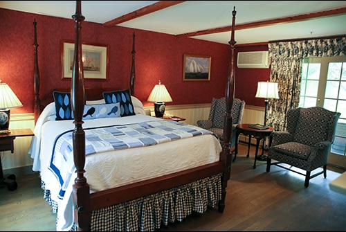 Wild Hunter guest room showing queen four poster bed with blue quilted bedding, red wallpaper, and wingback reading chairs