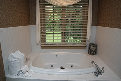 Wild Hunter guest bath with white tiled soaking tub, white towels and window