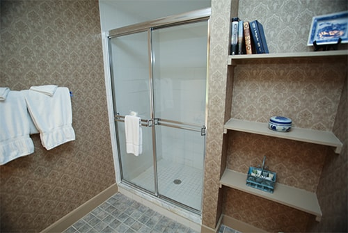 Wild Hunter bathroom showing large stall shower with sliding door and beige paisley wall paper