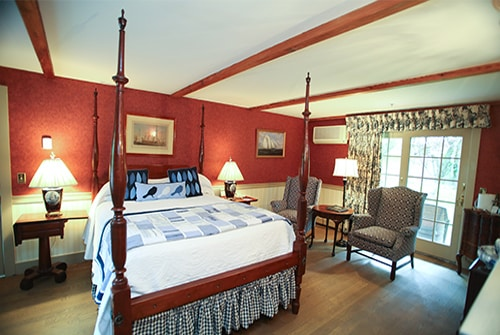 Wild Hunter guest room showing queen four poster antique bed, wingback reading chairs, and sliding door leading to private outdoor sitting area