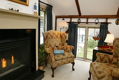Wild Pigeon guest room showing sunken sitting area with beige wingback reading chairs and gas fireplace