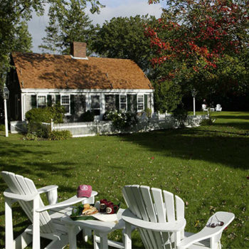 Two white Adirondack chairs and small table in the grass by a white sided cottage with white picket fence