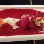 White rectangular plate topped with beet gazpacho
