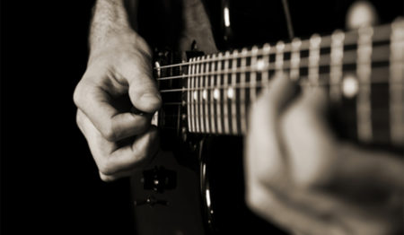 close-up view of man playing a guitar