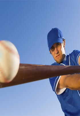 Close-up view of a man in blue with blue cap hitting a baseball with a bat