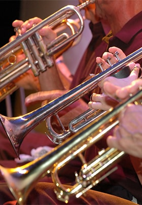 Close-up view of several people playing trumpets