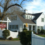 Exterior view of Captain's House Inn with white picket fence, bare trees and blue skies