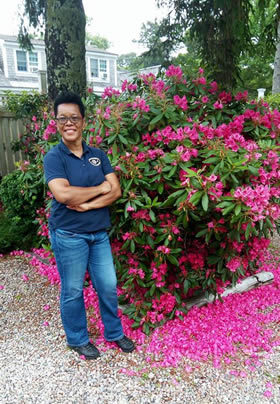 Smiling Woman standing outside next to fuscia rhododendron tree
