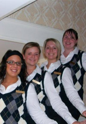 Four women in argyle vests smiling and standing on the stairway