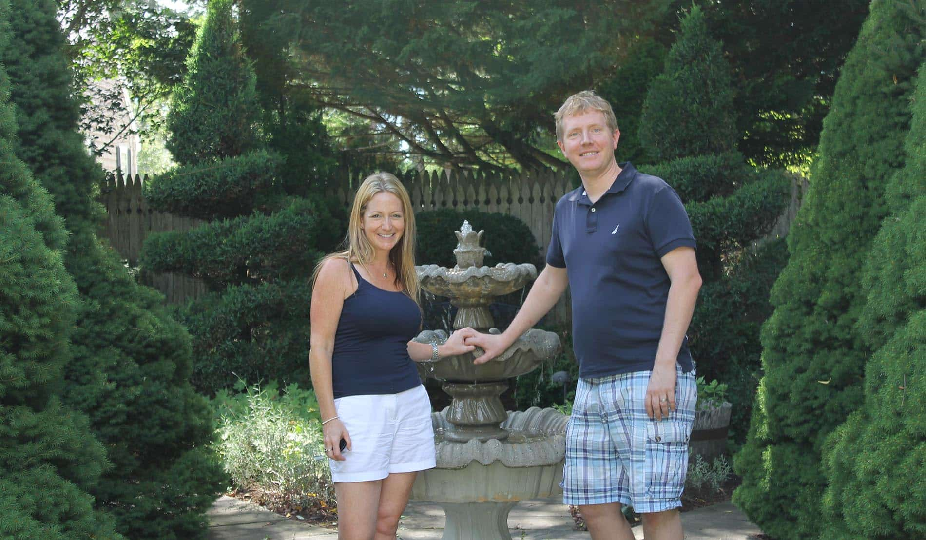 Man and woman holding hands standing in front of a three-tiered water fountain surrounded by manicured shrubs